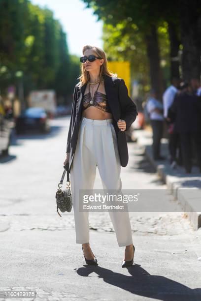 Lena Perminova wears sunglasses, a black blazer jacket, white pants, a Dior Saddle bag, bras, golden necklace, outside Alexandre Vauthier, during...