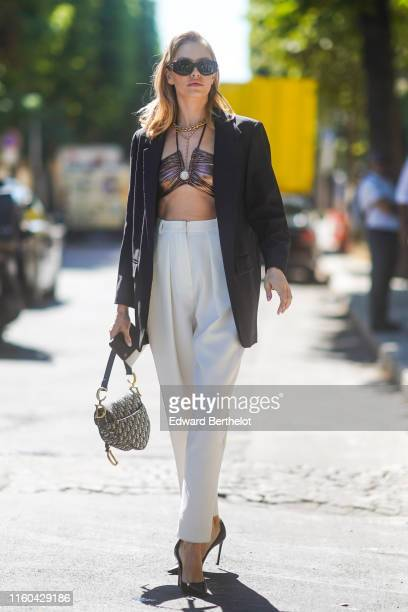 Lena Perminova wears sunglasses, a black blazer jacket, white pants, a Dior Saddle bag, bras, golden necklace, outside Alexandre Vauthier, during...