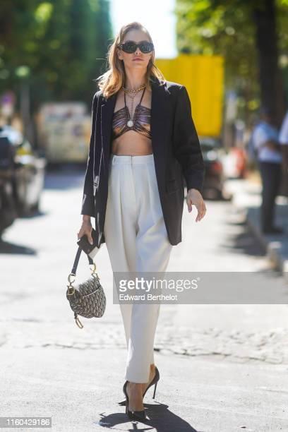 Lena Perminova wears sunglasses a black blazer jacket white pants a Dior Saddle bag bras golden necklace outside Alexandre Vauthier during Paris...