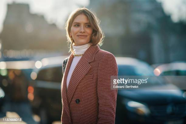 Lena Perminova wears sunglasses a red checked blazer jacket dress a white turtleneck a golden necklace a bag with printed shoulder strap outside...