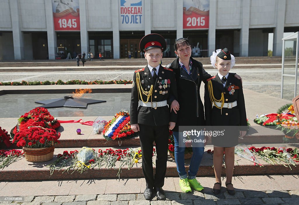 Lena Pimyenova (C) poses with her children Dima, 14, and Lena, 11, both military cadets, for a photo at the Eternal Flame at the grand memorial to Soviet soldiers killed during World War II at Victory Park ahead of celebrations to mark the 70th anniversary of the victory over Nazi Germany and the end of World War II on May 8, 2015 in Moscow, Russia. The city of Moscow will celebrate the anniversary on May 9 with a Victory Day international military parade and other events that most European leaders are snubbing because they accuse Russia of involvement in the war in eastern Ukraine.