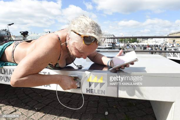 Lena Salmi recharges her mobile phone while sunbathing on a solar panel bench in Helsinki Finland on July 9 2018 The solar panel bench can be used...