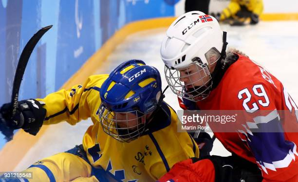 Lena Schroeder of Norway battles for the puck with Peter Nilsson of Sweden in the Ice Hockey Preliminary Round Group A game between Norway and Sweden...