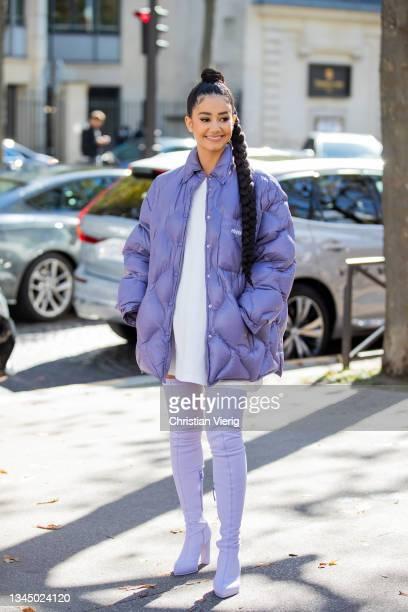 Lena Situation seen wearing purple down feather jacket, overknees boots, white dress outside Miu Miu during Paris Fashion Week - Womenswear Spring...