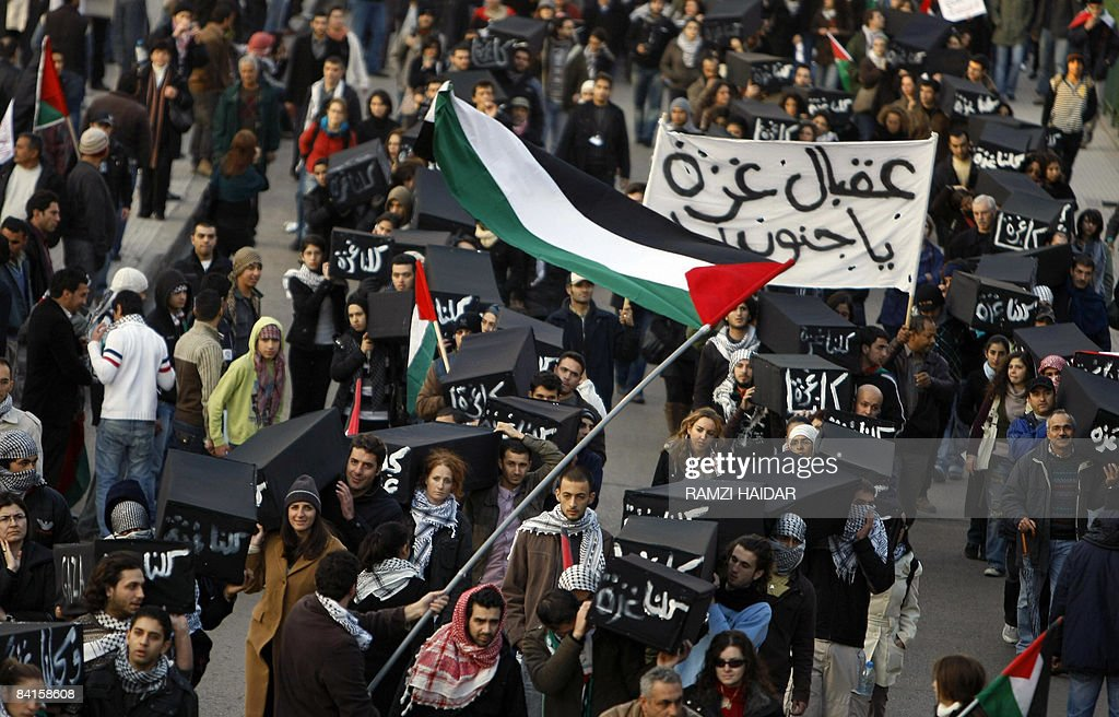 Lenansese protestors wave the Palestinian flag and carry fake coffins wrapped in black with the Arabic writing 'All of us are Gaza' marches to the Egyptian embassy in Beirut on January 2, 2009 during a protest against Israel's continuing bombardment of the Gaza Strip. Thousands of protestors joined rallies all over Lebanon today to condemn Israel's deadly raids on the Gaza Strip and what demonstrators called Egypt's complicity in the attacks. The Israeli offensive, launched on December 27 in response to a wave of rockets fired from Gaza, has killed at least 430 people and more than 2,250 others are wounded.