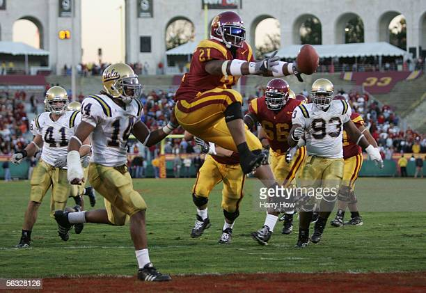 LenDale White of the USC Trojans jumps in the end zone for a touchdown against Tom Malone and Lawrence Miles of the UCLA Bruins December 3, 2005 at...
