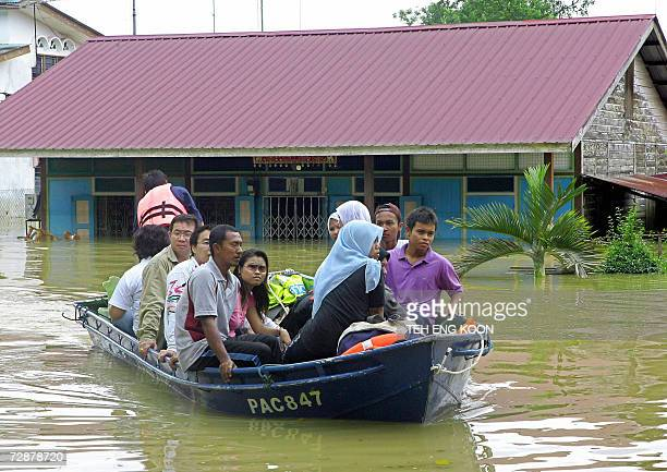 Rescuers transport civilians through waters at the flooded village of Lenga Muar in the southern Malaysian state of Johor 27 December 2006 Malaysia's...