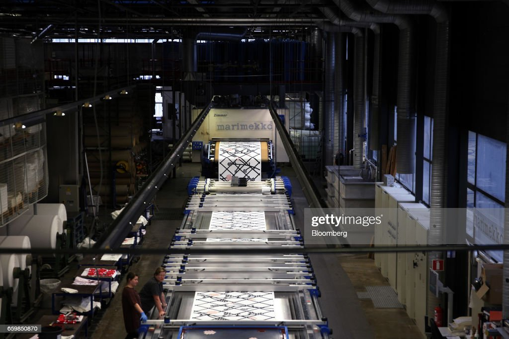 A length of fabric passes through a screen printing machine at the