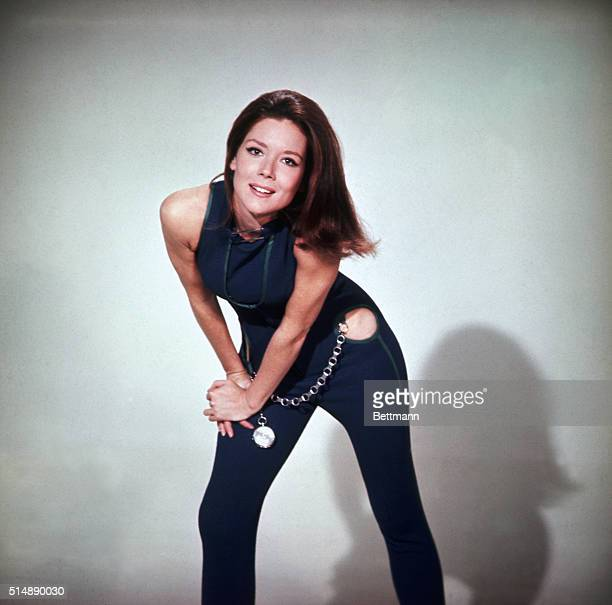 Length pose of Diana Rigg as Emma Peel in The Avengers. In this shot, Rigg is wearing a blue, one piece pants suit with cut out hips and an oversized...
