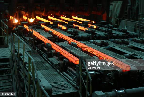 Lengths of red hot steel emerge from a shaping machine in the rolling shop at the Oskol Elektrometallurgical Plant steel mill operated by...