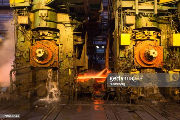 Lengths of red hot steel pass through a machine in the hot rolling shop at the Novolipetsk Steel PJSC plant operated by NLMK Group in Lipetsk Russia...