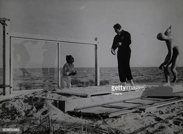 Leni Riefenstahl filming with a discus thrower the prologue to the Olympia film in the dunes of the Curonian Spit. September 30th of 1936. Photograph.