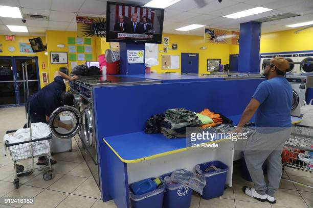 Lenin Rosales does his laundry at the Coral Way Lavanderia coin laundry as he watches a television broadcast of US President Donald Trump as he...