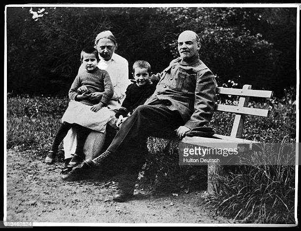 Lenin sits on a bench with his wife Krupskaya their nephew Victor and Vera a worker's daughter