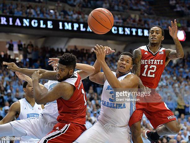 Lennard Freeman and Anthony Barber of the North Carolina State Wolfpack battle Kennedy Meeks of the North Carolina Tar Heels for a rebound during...