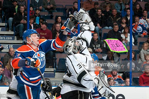 Lennart Petrell of the Edmonton Oilers reaches for the puck while Jonathan Quick of the Los Angeles Kings hangs on to the puck at Rexall Place on...