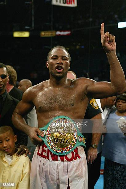 Lennox Lewis celebrates with this championship belts after knocking out Mike Tyson in the 8th round during their WBC/IBF heavyweight championship...