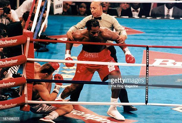 Lennox Lewis is pulled back by the referee after knocking out Andrew Golota during the fight at Caesar's Hotel Casino on October 41997 in Atlantic...