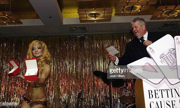 Lenny Clark right auctions off jewelry with assistance from Julie Atlas Muz glitter girl at the Cam Neely Foundation For Cancer Celebrity Fundraiser...