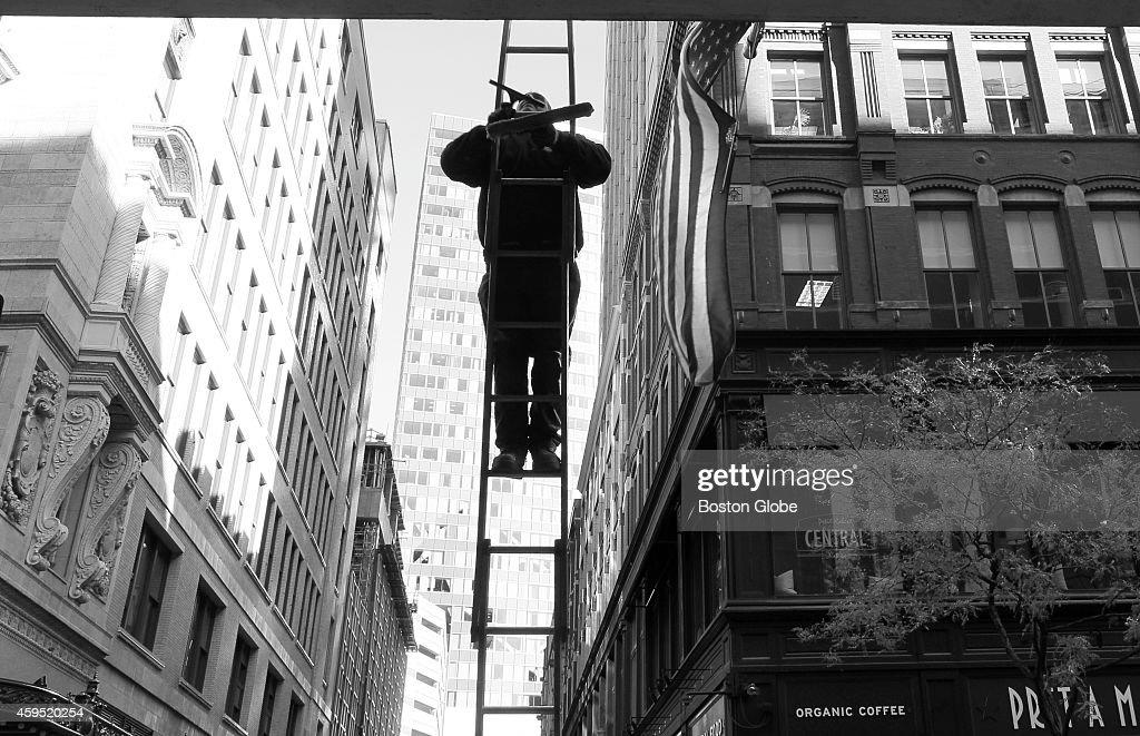 Lenny Gaeta, of Gaeta Window Cleaning, on ladder working on Macy's Downtown Crossing Thursday morning.