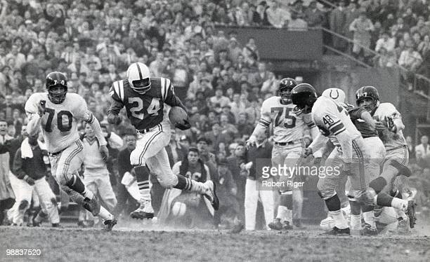 Lenny Moore of the Baltimore Colts runs with the ball against Sam Huff and Bill Stits of the New York Giants during the 1959 NFL Championship game at...