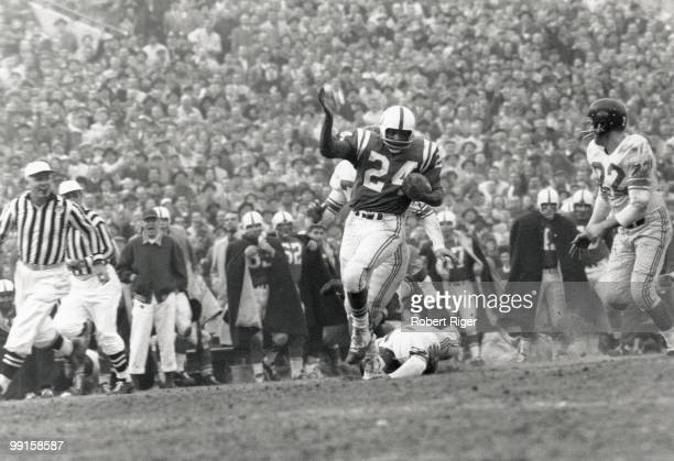 Lenny Moore of the Baltimore Colts runs with the ball as Sam Huff and Bill Stits of the New York Giants go for the tackle as Dick Lynch of the Giants...