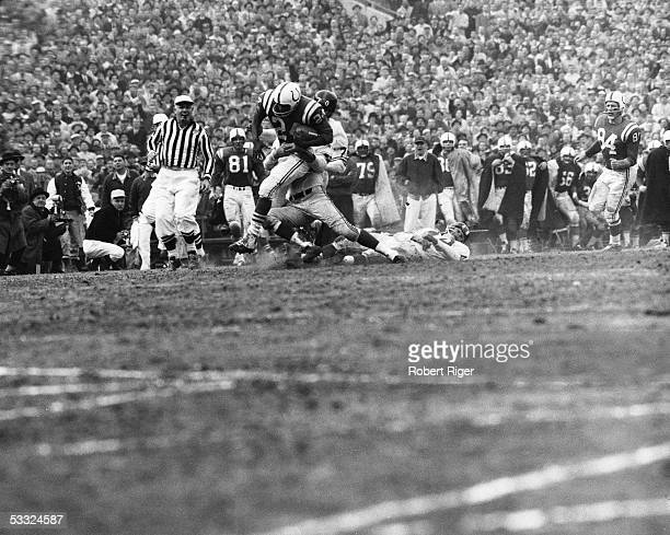 Lenny Moore of the Baltimore Colts runs with the ball as Sam Huff Bill Stits and Dick Lynch of the New York Giants go for the tackle during the 1959...