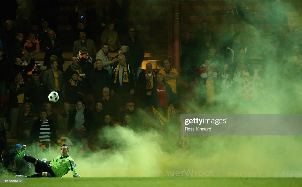 Lenny Pidgeley of Newport clears the ball as fans let off a flair during the Blue Square Bet Premier Conference Play-off: First Leg match between Grimsby Town and Newport County at Blundell Park on April 24, 2013 in Grimsby, England.