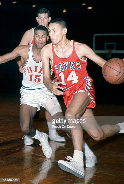 Lenny Wilkens of the St Louis Hawks drives past Hal Greer of the Philadelphia 76ers during an NBA basketball game circa 1965 at Convention Hall in...