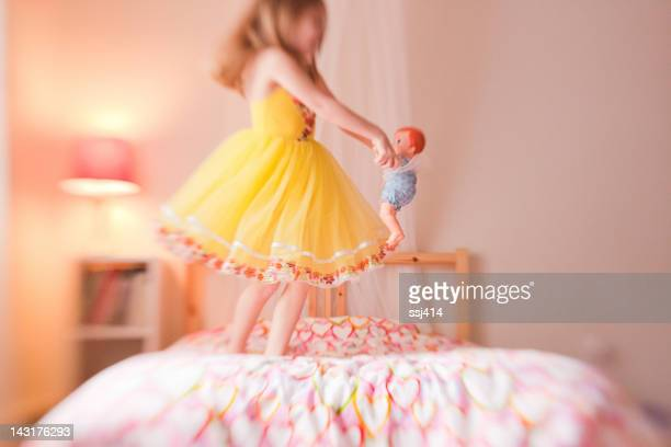 Lens baby image of little girl spinning with her doll