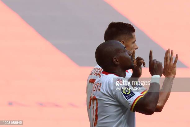 Lens' Congolese midfielder Gael Kakuta celebrates with teammate Florian Sotoca and other teammates after scoring a penalty during the French L1...