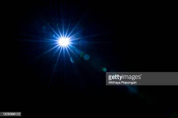 lens flare against black background - blendenfleck stock-fotos und bilder