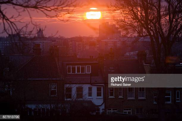 Lens flare from setting sun between layers of cloud over innercity south London rooftops As the sun sinks inn the winter sky over the innercity of...