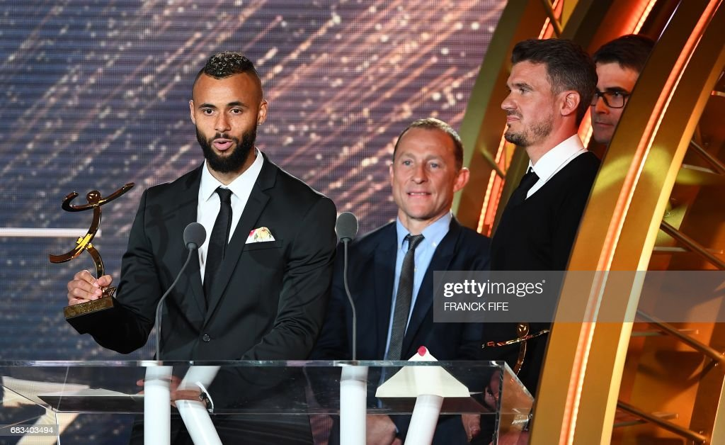 Lens' forward John Bostock (L) receives the Best Ligue 2 player award from French former player Jean Pierre Papin (C) next to Best Ligue 2 goalkeeper Nicolas Douchez, during the 26th edition of the UNFP (French National Professional Football players' Union) trophies ceremony at the Pavillon d'Armenonville in Paris, on May 15, 2017. /