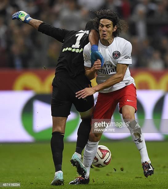 Lens' French goalkeeper Rudy Riou vies with Paris Saint-Germain's Uruguyan forward Edinson Cavani during the French L1 football match between RC Lens...