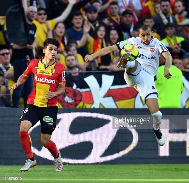Lens' French midfielder Fabien Centonze vies with Dijon's French defender Fouad Chafik during the French L1L2 first leg playoff football match...