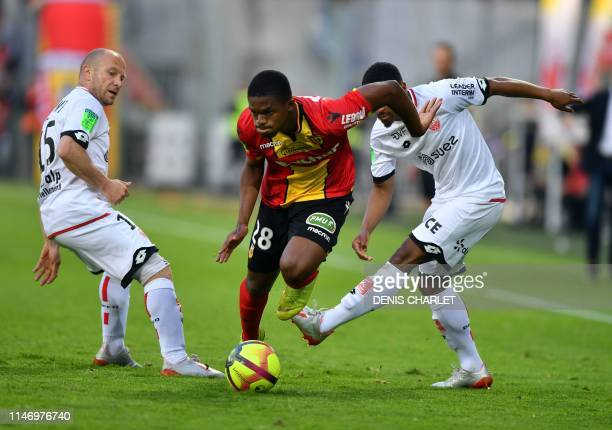 Lens' Malian midfielder Cheick Doucoure vies with Dijon's French midfielder Florent Balmont and Dijon's French midfielder Senou Coulibaly during the...