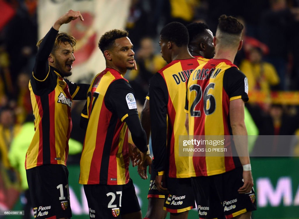 Lens' midfielder Kenny Lala (C) celebrates with his teammates after scoring during the French L2 football match between Lens and Strasbourg on May 8, 2017 at the Bollaert-Delelis stadium in Lens. /