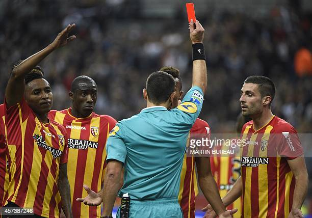 Lens' players react as Lens' French defender Jean-Philippe Gbamin receives a red card for two yellow cards during the French L1 football match...