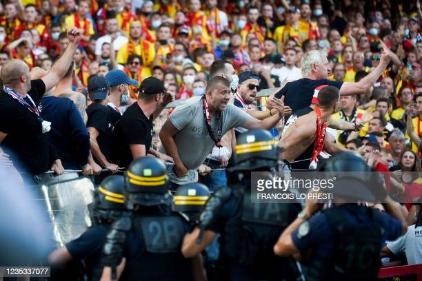 Lens' supporters clash with riot police officers during the French L1 football match between RC Lens and Lille at Stade Bollaert-Delelis in Lens,...