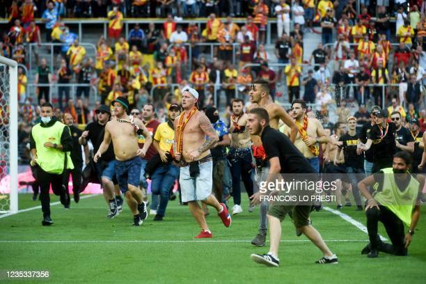 Lens' supporters invade the pitch during the French L1 football match between RC Lens and Lille at Stade Bollaert-Delelis in Lens, northern France,...