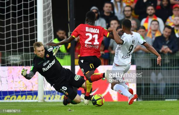 Lens's French defender Massadio Haidara vies with Dijon's French forward Wesley Said and Lens's French goalkeeper Jeremy Vachoux during the French...