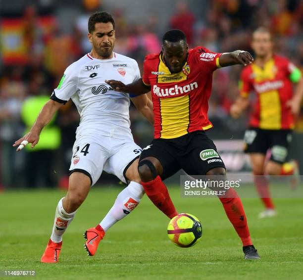 Lens's Senegalese midfielder Arthur Yannick Gomis vies with Dijon's French defender Wesley Lautoa during the French L1L2 first leg playoff football...