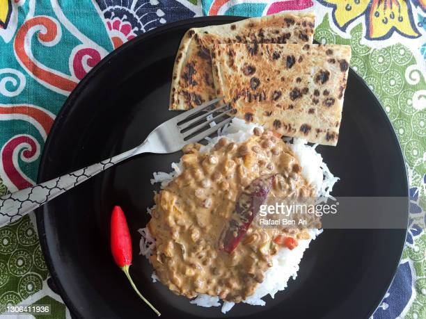 lentils curry served in a plate with rice naan bread and hot chili - rafael ben ari - fotografias e filmes do acervo