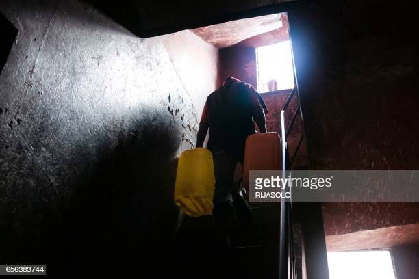Leo a Madagascan man with a wife and two children carries filled jerrycans up a stairwell after filling them at a public fountain during a period...