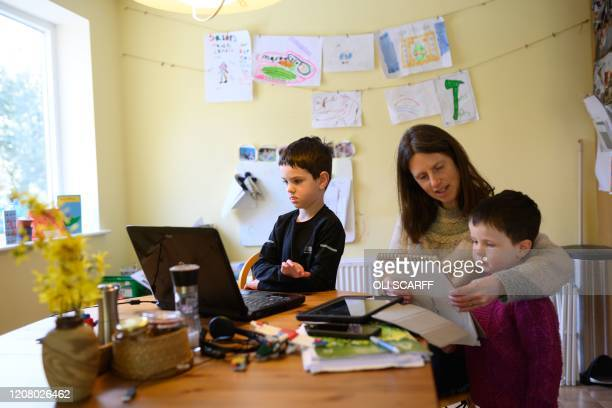 Leo aged 6 and Espen aged 3 are assisted by their mother Moira as they homeschool and navigate online learning resources provided by their infant...