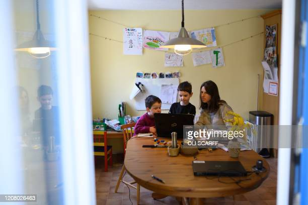Leo , aged 6, and Espen, aged 3, are assisted by their mother Moira as they navigate online learning resources provided by their infant school in the...