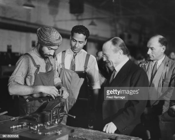 Leo Amery or L S Amery the Secretary of State for India and Burma watches Mr A B Singh from Bihar in India during munitions training in the UK 1941 A...