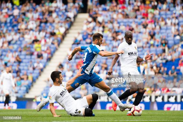 Leo Baptistao of RCD Espanyol conducts the ball under pressure from Jose Gaya and Geoffrey Kondogbia of Valencia CF during the La Liga match between...