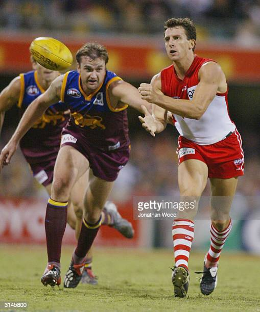 Leo Barry of the Swans gets a hand pass away during the first round AFL match between the Brisbane Lions and the Sydney Swans played at the Gabba...